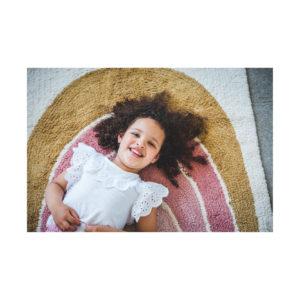 Meisje ligt op regenboog tapijt van Tapis Petit