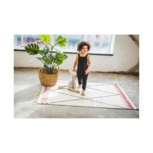 Kindje op tapijt met ruit met roze bies van Tapis Petit